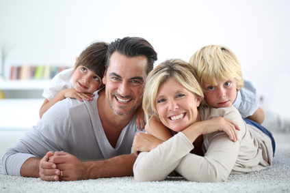 Portrait of happy family laying on carpet
